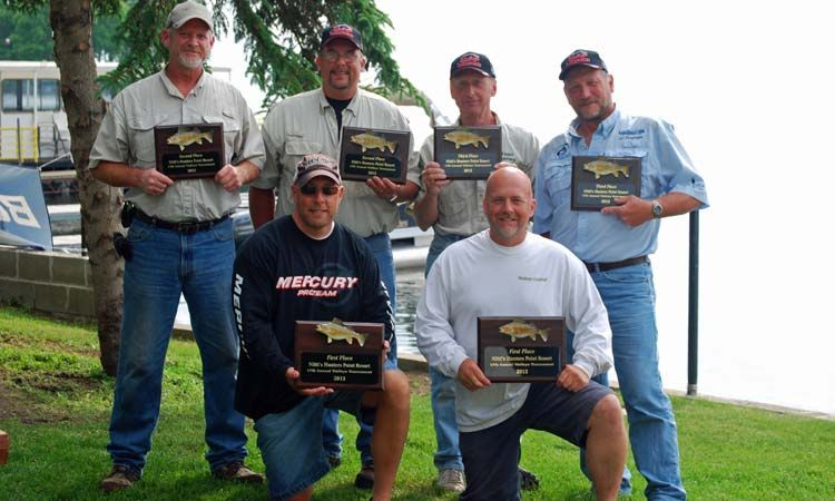 fishing tournament winners holding plaques at lake mille lacs